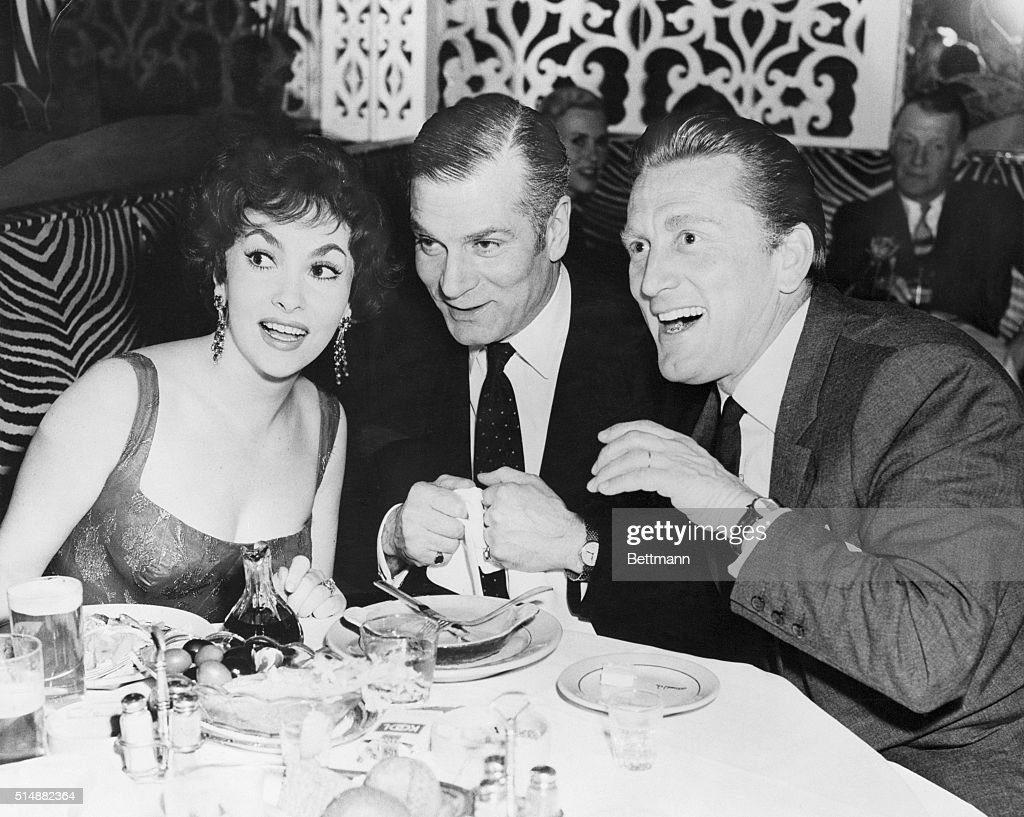 Gina Lollobrigida with Laurence Olivier (C) and Kirk Douglas during her farewell party at the El Morocco in New York City.