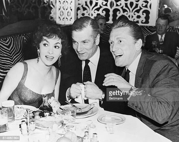 Gina Lollobrigida with Laurence Olivier and Kirk Douglas during her farewell party at the El Morocco in New York City