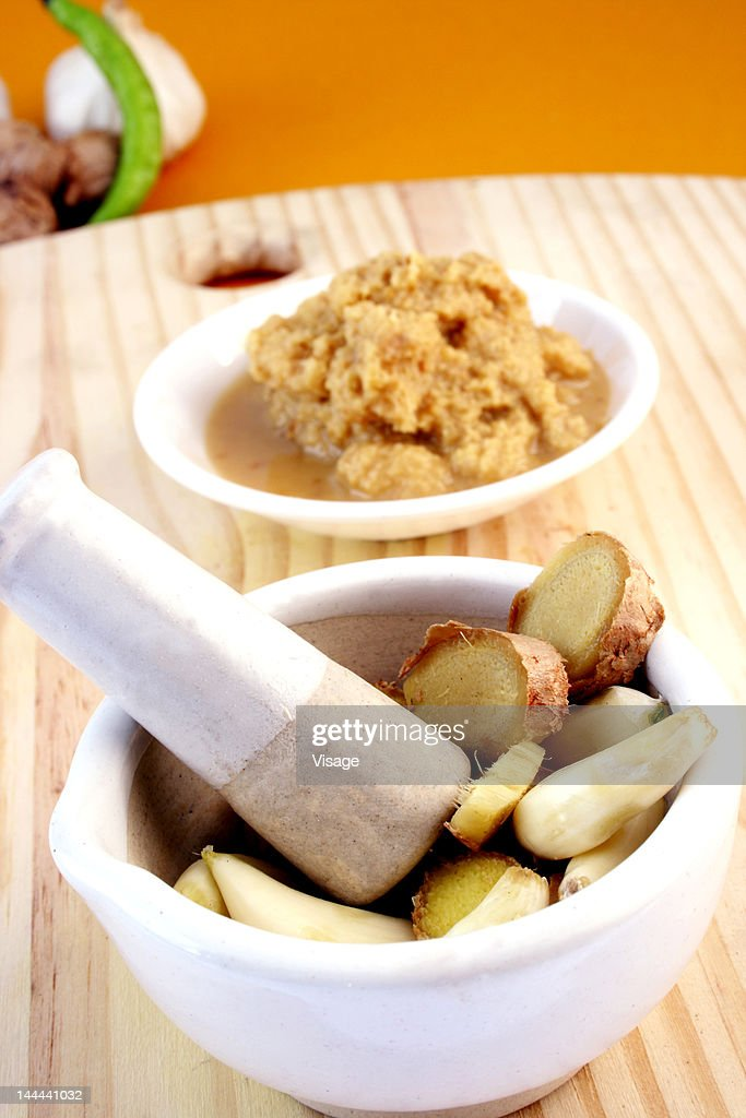 Ginger and garlic in a mortar with pestle by ginger and garlic paste