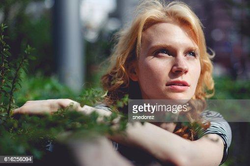 Ginger girl holding hands green branch bush photo toned : Stock Photo