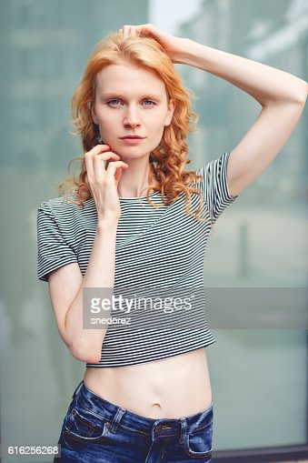 Ginger girl on background of building, photo toned : Stock Photo