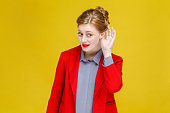 Ginger red head woman in red suit listening secret. Studio shot, isolated on yellow background