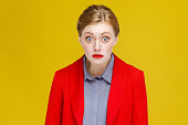 Ginger red head woman in red suit wonder. Studio shot, isolated on yellow background
