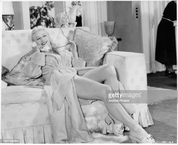 Ginger Rogers on phone only wearing a bathrobe in a scene from the film 'Twist Of Fate' 1954