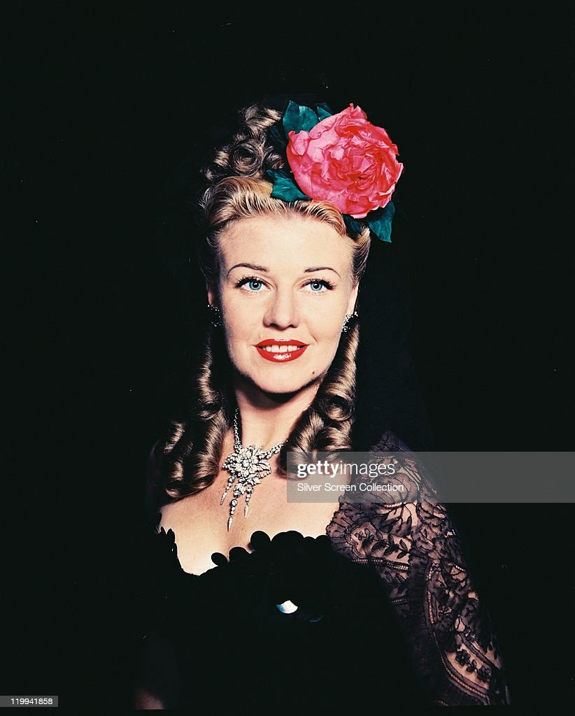 <a gi-track='captionPersonalityLinkClicked' href=/galleries/search?phrase=Ginger+Rogers&family=editorial&specificpeople=93466 ng-click='$event.stopPropagation()'>Ginger Rogers</a> (1911-1995), US actress and dancer, wearing a black outfit with black lace sleeves, with a red flower in her hair which has been styled in ringlets in a studio portrait, against a black background, circa 1945.