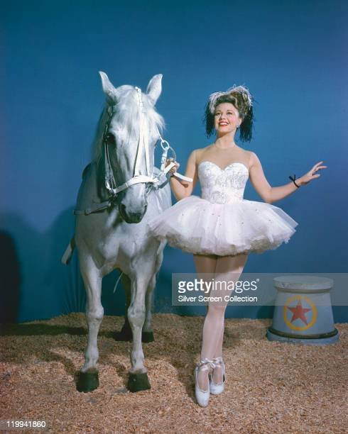 Ginger Rogers US actress and dancer wearing a white tutu and ballet shoes while holding a white horse with sawdust on the ground in a studio portrait...