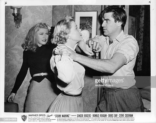 Ginger Rogers watches in horror as Doris Day and Steve Cochran fight in a scene from the film 'Storm Warning' 1951