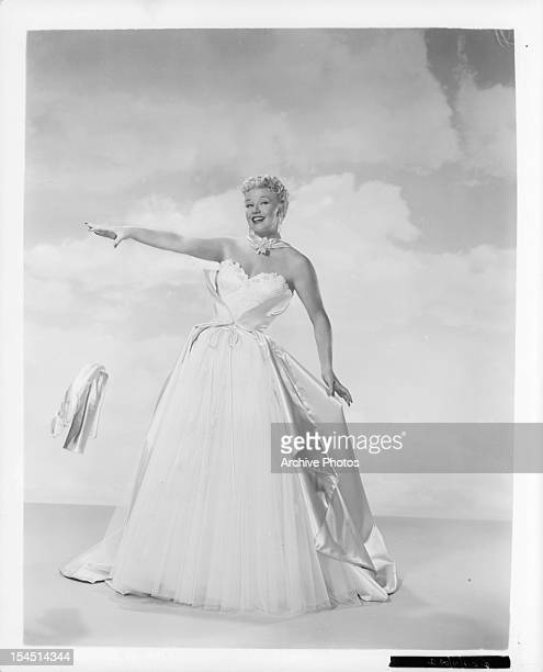 Ginger Rogers wears a white dress in a promotional portrait for the film 'Black Widow' 1954