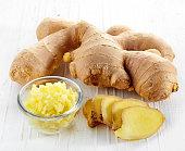 Fresh sliced ginger root on white wooden background
