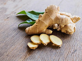 Ginger root slice with leaf and has a spicy taste on wooden background