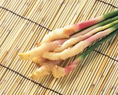 Ginger roots on bamboo mat, high angle view
