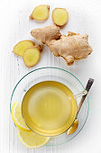 Ginger tea and fresh ginger root on white wooden background top view