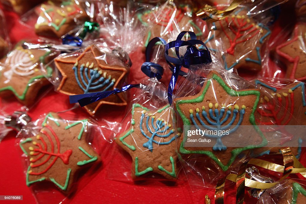 Gingerbread cookies in the shape of Stars of David and decorated with a Hanukkiah lie for sale at a baker's stall at the annual Hanukkah market at...