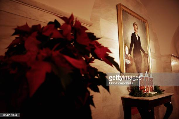 A gingerbread house and poinsettias decorate a portrait of former first lady Hillary Clinton in the hallway on the ground floor during the first...
