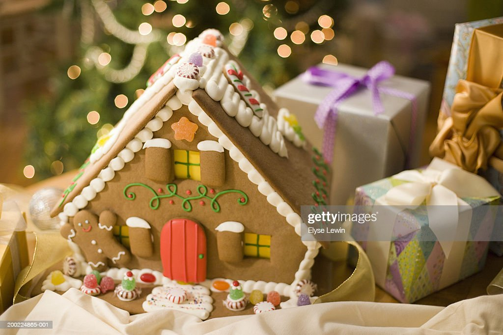 Gingerbread house next to Christmas gifts