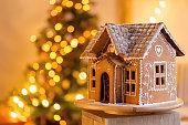 gingerbread house over defocused lights of Chrismtas decorated fir tree. Christmas eve, warm atmospheric light