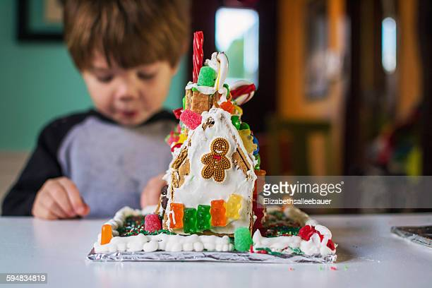 Gingerbread house with boy eating candy in background