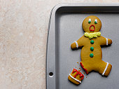 Gingerbread man with broken leg on baking sheet, close-up