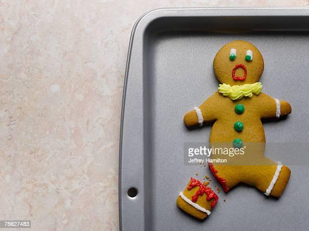 Gingerbread man with broken leg on baking sheet, close-up