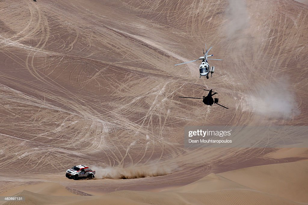 Giniel De Villiers of South Africa and Dirk Von Zitzewitz of Germany for Imperial Toyota compete as the helicopter flies overhead in stage 9 during Day 10 of the 2014 Dakar Rally on January 14, 2014 in Iquique, Chile.
