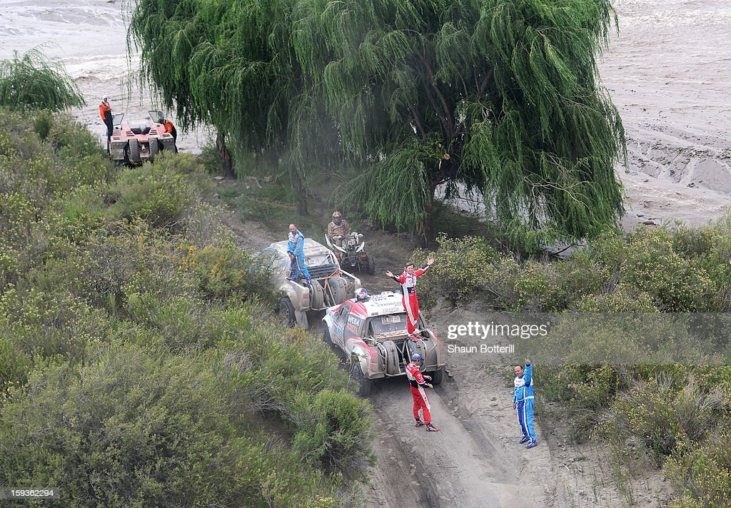 Giniel De Villiers signals to the helicopter after the stage from Salta to Tucuman was interupted by a flash flood during the 2013 Dakar Rally on January 12, 2012 in Salta, Argentina.