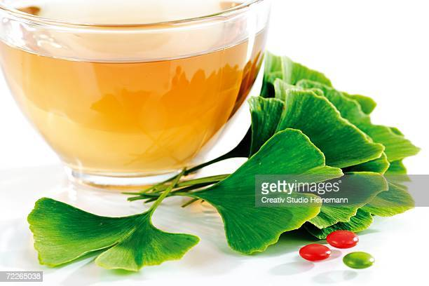 Herbal tea in cup with ginkgo leaves and pills, close-up