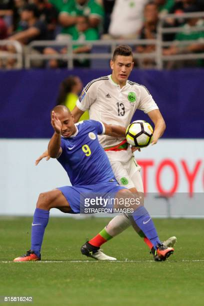 Gino van Kessel of Curacao and Cesar Montes of Mexico fight for the ball during a Group C match between Mexico and Curacao as part of CONCACAF Gold...