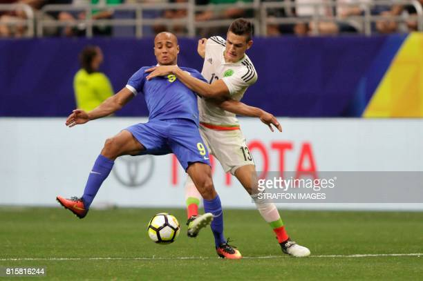 Gino van Kessel of Curacao fights for the ball with Cesar Montes of Mexico during a Group C match between Mexico and Curacao as part of CONCACAF Gold...