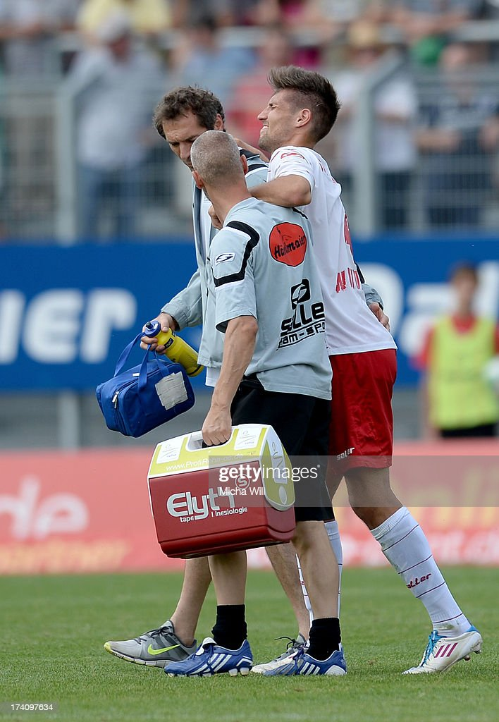 Gino Windmueller (R) of Regensburg leaves the pitch after picking up an injury during the Third League match between Jahn Regensburg and SpVgg Unterhaching at Jahnstadion on July 20, 2013 in Regensburg, Germany.