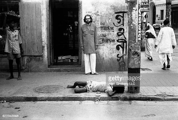Ginsberg stands near a young Indian boy lying on the sidewalk as if homeless