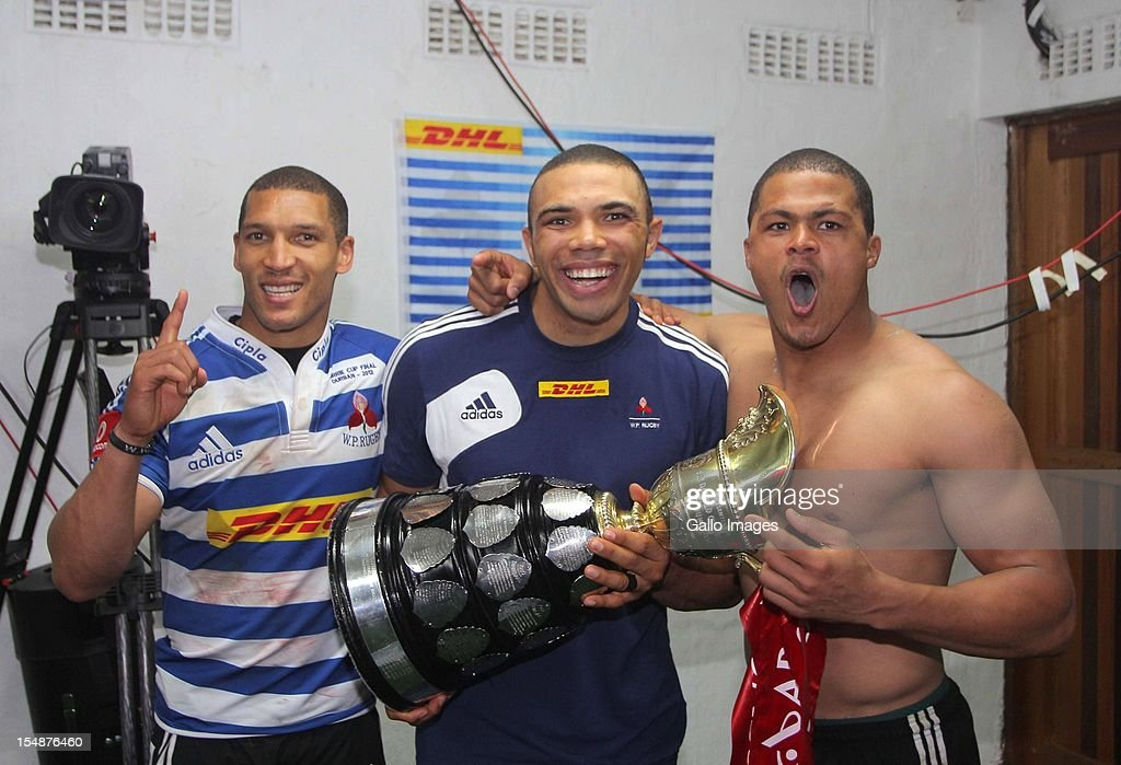Gio Aplon Bryan Habana and Juan de Jongh of Western Province celebrate with the trophy after the Absa Currie Cup final match between The Sharks and...