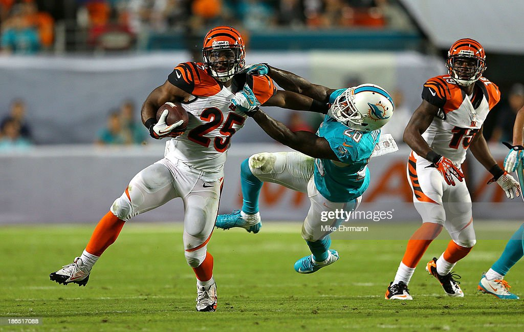 Gio Bernard #25 of the Cincinnati Bengals is grabbed by Reshad Jones #20 of the Miami Dolphins during a game at Sun Life Stadium on October 31, 2013 in Miami Gardens, Florida.