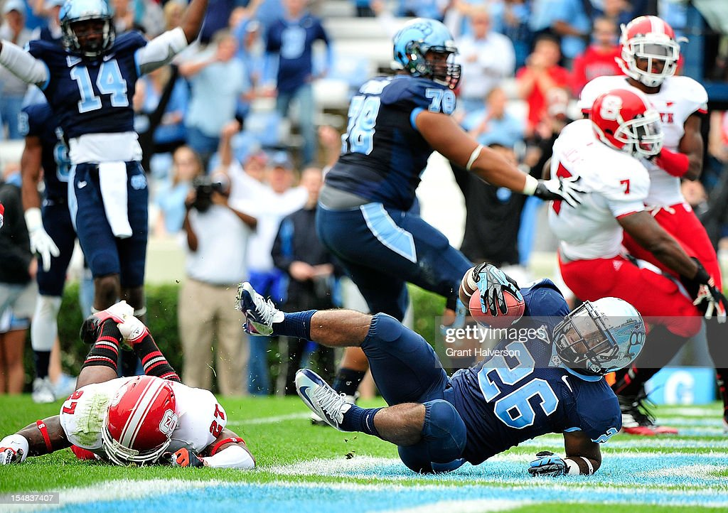 Gio Bernard #26 of the North Carolina Tar Heels divs over Earl Wolff #27 of the North Carolina State Wolfpack for a touchdown during play at Kenan Stadium on October 27, 2012 in Chapel Hill, North Carolina.