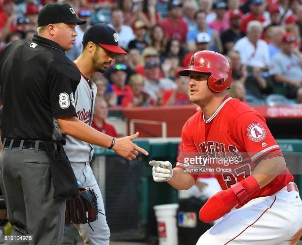 Gio Gonzalez of the Washington Nationals looks on as Umpire Cory Blaser watches as Mike Trout of the Los Angeles Angels crosses the plate for a run...