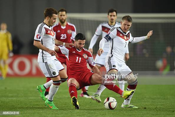 Giorgi Chanturia of Georgia is challenged by Mario Goetze of Germany and Bastian Schweinsteiger of Germany during the EURO 2016 Group D Qualifier...