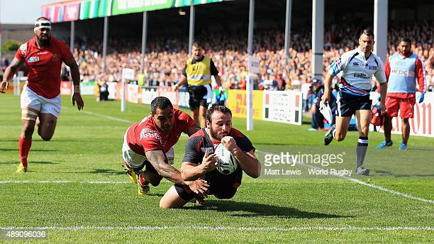 Giorgi Tkhilaishvili of Georgia holds off Sione Piukala of Tonga to score a try during the 2015 Rugby World Cup Pool C match between Tonga and...