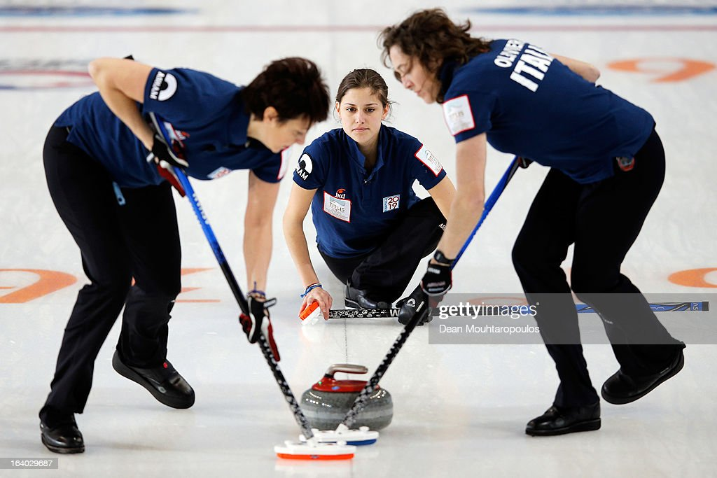 Giorgia Apollonio (C) of Italy looks on after throwning the stone as Chiara Olivieri (R) and Claudia Alvera (L) sweep in the match between Japan and Italy on Day 4 of the Titlis Glacier Mountain World Women's Curling Championship at the Volvo Sports Centre on March 19, 2013 in Riga, Latvia.