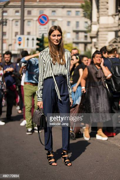 Giorgia Tordini wears a silk black and white stripped top with loose ends and high wasited blue trousers uring the Milan Fashion Week Spring/Summer...