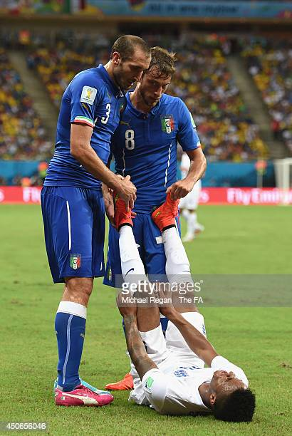 Giorgio Chiellini and Claudio Marchisio of Italy help Raheem Sterling of England stretch during the 2014 FIFA World Cup Brazil Group D match between...