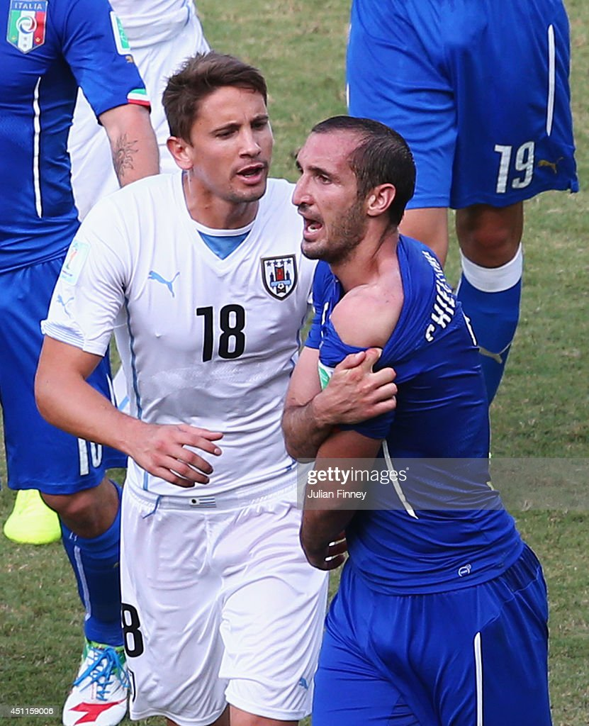 <a gi-track='captionPersonalityLinkClicked' href=/galleries/search?phrase=Giorgio+Chiellini&family=editorial&specificpeople=605793 ng-click='$event.stopPropagation()'>Giorgio Chiellini</a> of Italy pulls down his shirt after a clash with Luis Suarez of Uruguay (not pictured) as <a gi-track='captionPersonalityLinkClicked' href=/galleries/search?phrase=Gaston+Ramirez&family=editorial&specificpeople=6335880 ng-click='$event.stopPropagation()'>Gaston Ramirez</a> of Uruguay looks on during the 2014 FIFA World Cup Brazil Group D match between Italy and Uruguay at Estadio das Dunas on June 24, 2014 in Natal, Brazil.