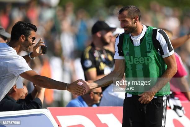 Giorgio Chiellini of Juventus A salutes a fan during the preseason friendly match between Juventus A and Juventus B on August 17 2017 in Villar...