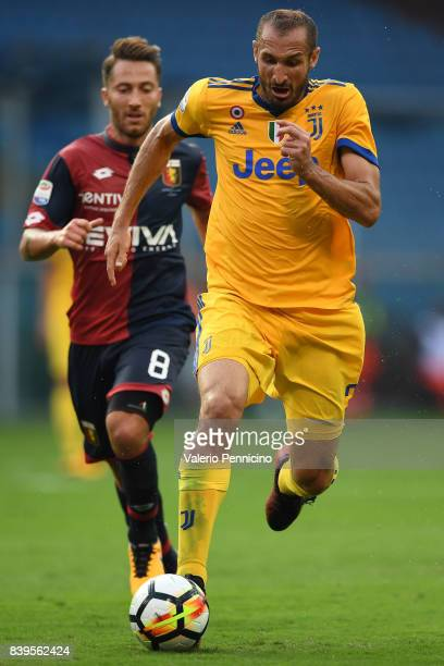 Giorgio Chiellini of Juventus in action against Andrea Bertolacci of Genoa CFC is challenged by during the Serie A match between Genoa CFC and...