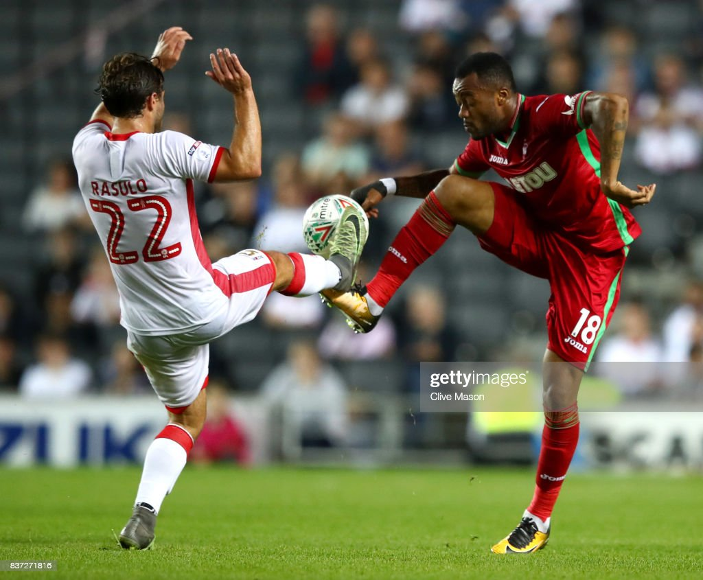 Giorgio Rasulo of Milton Keynes Dons fouls Jordan Ayew of Swansea City during the Carabao Cup Second Round match between Milton Keynes Dons and Swansea City at StadiumMK on August 22, 2017 in Milton Keynes, England.