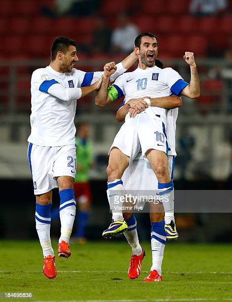 Giorgos Karagounis of Greece celebrates scoring with team mates Kostas Katsouranis and Dimitris Siovas after scoring his team's second goal during...