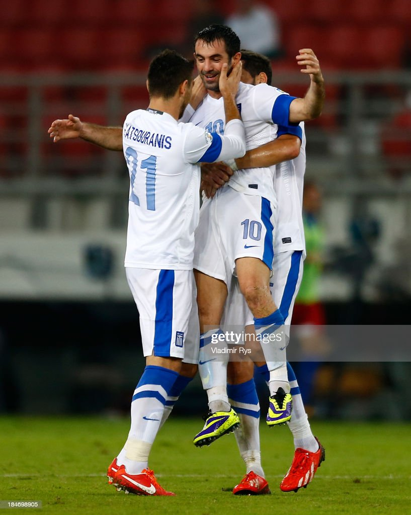 <a gi-track='captionPersonalityLinkClicked' href=/galleries/search?phrase=Giorgos+Karagounis&family=editorial&specificpeople=240229 ng-click='$event.stopPropagation()'>Giorgos Karagounis</a> of Greece is celebrated by his team mates Kostas Katsouranis (L) and Dimitris Siovas after scoring his team's second goal during the group G FIFA 2014 World Cup Qualifier match between Greece and Liechtenstein at Karaiskakis Stadium on October 15, 2013 in Athens, Greece.