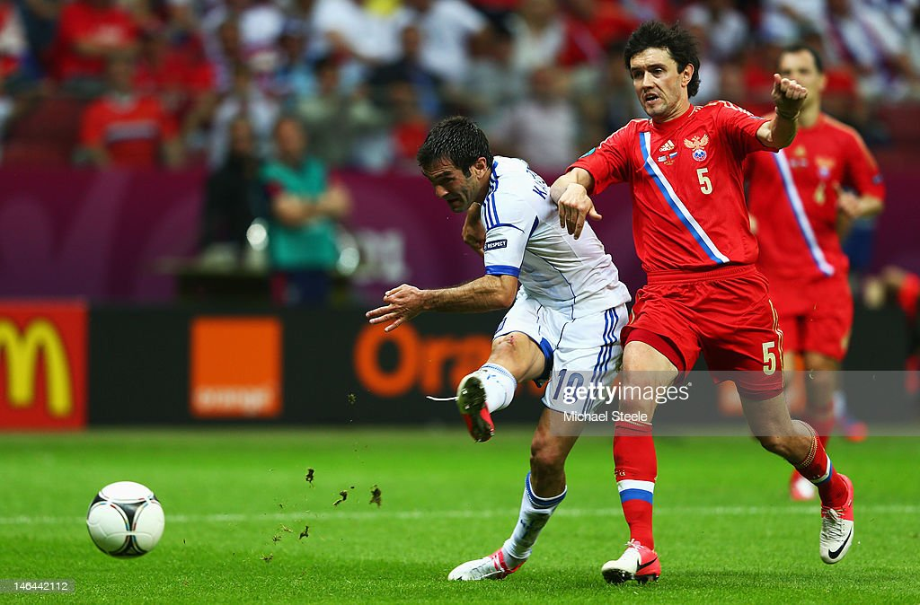 Giorgos Karagounis of Greece scores the opening goal under pressure from Yuriy Zhirkov of Russia during the UEFA EURO 2012 group A match between Greece and Russia at The National Stadium on June 16, 2012 in Warsaw, Poland.