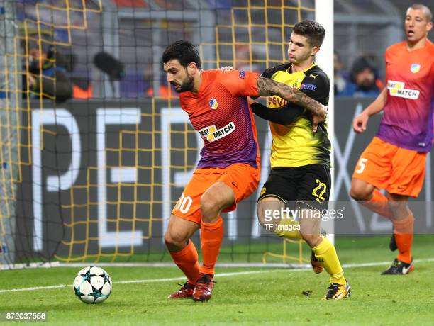 Giorgos Merkis of APOEL Nicosia and Christian Pulisic of Dortmund battle for the ball during the UEFA Champions League Group H soccer match between...