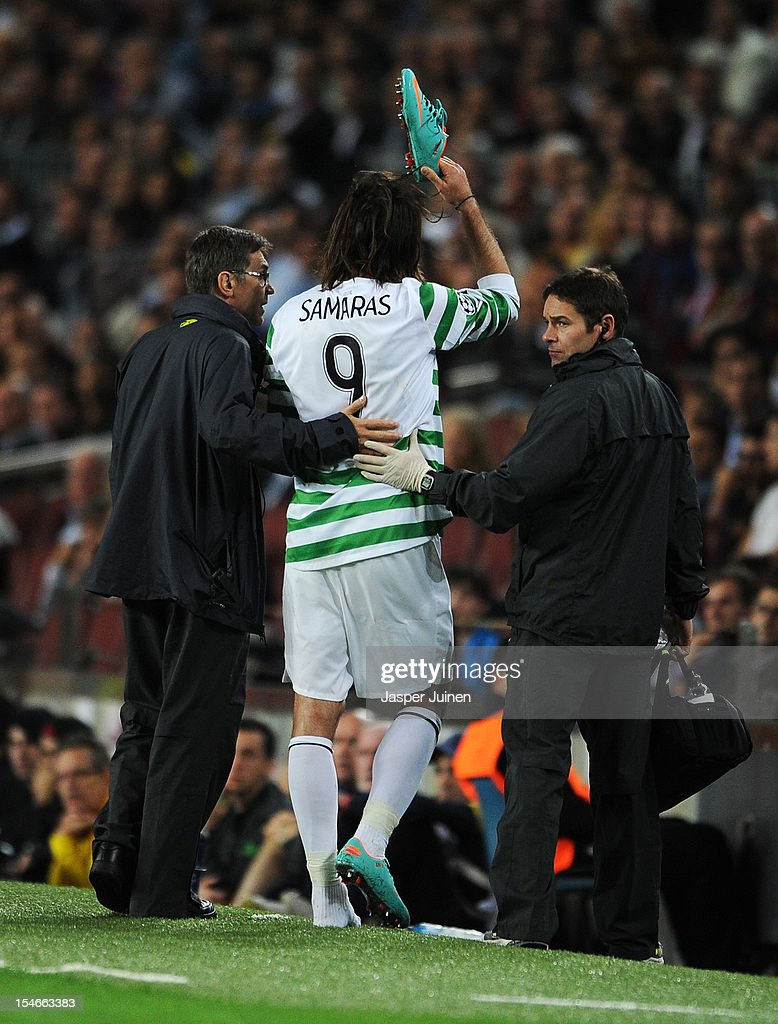 Giorgos Samaras (C) of Celtic FC reacts while being helped off the pitch after injuring himself during the UEFA Champions League group G match between FC Barcelona and Celtic FC at the Camp Nou stadium on October 23, 2012 in Barcelona, Spain.