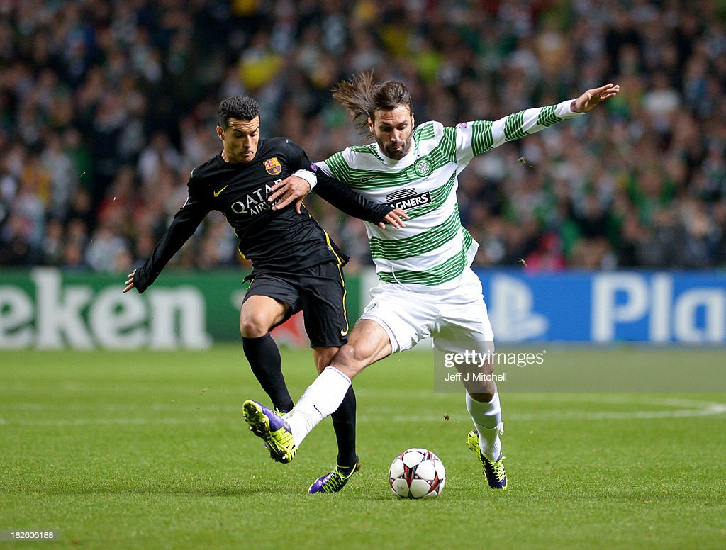 Giorgos Samaras of Celtic holds off Pedro of Barcelona during the UEFA Champions League Group H match between Celtic and FC Barcelona at Celtic Park Stadium on October 1, 2013 in Glasgow, Scotland.