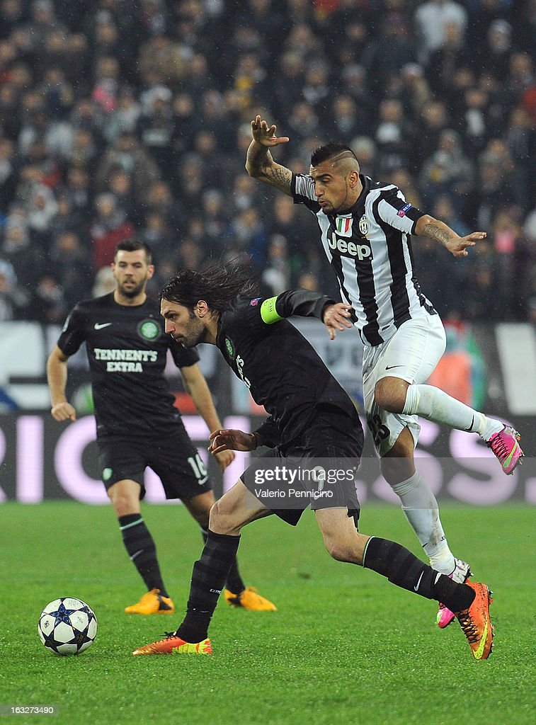 Giorgos Samaras (L) of Celtic is challenged by Arturo Vidal of Juventus during the UEFA Champions League round of 16 second leg match between Juventus and Celtic at Juventus Arena on March 6, 2013 in Turin, Italy.